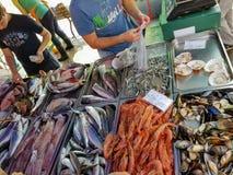 Marsaxlokk, Malta - mayo de 2018: El prepearing de los vendedores mucho clase de pescados y de camarones en contador en venta foto de archivo libre de regalías