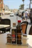 Marsaxlokk, Malta - Mei 2018: Kruid balsemieke azijn, zout, peper en olijfolie op de lijst in de koffie van de de zomerstraat stock afbeelding