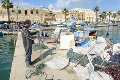 The fishing village of Marsaxlokk on Malta island. Marsaxlokk, Malta - 3 November 2017: fishermen preparing the fishing nets near their boat at Marsaxlokk on Stock Photo