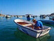 Marsaxlokk, Malta: 08 oktober: De niet geïdentificeerde oude mens bereidt vissersboot op 08 Oktober, 2014 in Marsaxlokk, Malta vo stock fotografie