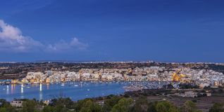 Marsaxlokk, Malta - Panoramic skyline view of Marsaxlokk, the tr. Aditional fisherman village of Malta at sunrise with blue sky and beautiful clouds Stock Images