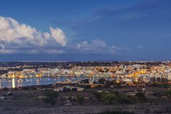Marsaxlokk, Malta - Panoramic skyline view of Marsaxlokk, the tr. Aditional fisherman village of Malta at sunrise with blue sky and beautiful clouds Stock Image