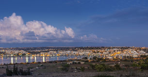 Marsaxlokk, Malta - Panoramic skyline view of Marsaxlokk. The traditional fisherman village of Malta at sunrise with blue sky and beautiful clouds Royalty Free Stock Image