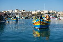 MARSAXLOKK, MALTA - SEP 6: native fishing boats in the ancient fishing village Marsaxlokk in Mediterranean sea on warm sunset hour. S on Sep 6, 2015. Panoramic Stock Photo
