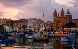 Marsaxlokk, Malta. Small fishing village on Sunday. Port and fishing boats Stock Photos