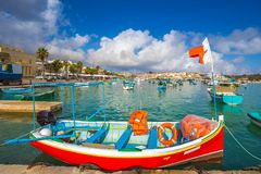 Marsaxlokk, Malta - Traditional colorful maltese Luzzu fisherboat at the old market of Marsaxlokk with turquoise sea water. And palm trees on a summer day Stock Photography