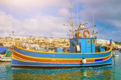 Marsaxlokk, Malta - Traditional colorful maltese Luzzu fisherboat at the old village of Marsaxlokk. With turquoise sea water on a bright summer day Stock Photos
