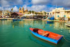 Marsaxlokk, Malta - Traditional colorful maltese Luzzu fisherboat at the old village of Marsaxlokk. With turquoise sea water, blue sky and palm trees on a Stock Image