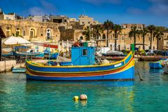 Marsaxlokk, Malta - Traditional colorful maltese Luzzu fisherboat at the old village of Marsaxlokk. With turquoise sea water and palm trees on a summer day Stock Photography