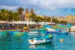 Marsaxlokk, Malta - Traditional colorful maltese Luzzu fisherboat at the old village of Marsaxlokk with turquoise sea water. And palm trees on a summer day Stock Photos