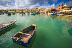 Marsaxlokk, Malta - Traditional colorful maltese Luzzu fisherboats at the old market of Marsaxlokk with green sea water, blue sky. And palm trees on a summer Royalty Free Stock Photography