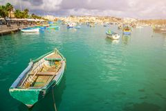Marsaxlokk, Malta - Traditional colorful maltese Luzzu fisherboats at the old market of Marsaxlokk with green sea water Royalty Free Stock Image