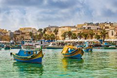 Marsaxlokk, Malta - Traditional colorful maltese Luzzu fisherboats at the old village of Marsaxlokk. With turquoise sea water and palm trees on a summer day Royalty Free Stock Photo