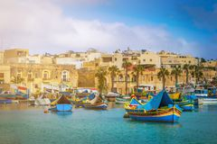Marsaxlokk, Malta - Traditional colorful maltese Luzzu fisherboats at the old village of Marsaxlokk with turquoise sea water. And palm trees on a summer day Royalty Free Stock Photo