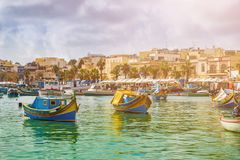 Marsaxlokk, Malta - Traditional colorful maltese Luzzu fisherboats at the old village of Marsaxlokk with turquoise sea water. And palm trees on a summer day Royalty Free Stock Photography