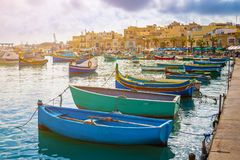 Marsaxlokk, Malta - Traditional colorful maltese Luzzu fisherboats at the old village of Marsaxlokk with turquoise sea water. And palm trees on a summer day Royalty Free Stock Images