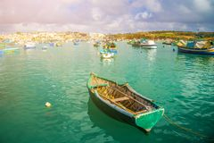 Marsaxlokk, Malta - Traditional green maltese Luzzu fisherboat. At the old market of Marsaxlokk with green sea water, blue sky and palm trees on a summer day Stock Image