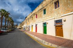 Marsaxlokk, Malta - Traditional maltese vintage house with orange, blue, yellow, red, green and brown doors and windows. With palm trees and blue sky Stock Photos