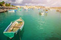 Marsaxlokk, Malta - Tradycyjni kolorowi maltese Luzzu fisherboats przy starym rynkiem Marsaxlokk z zieloną wodą morską Obraz Royalty Free