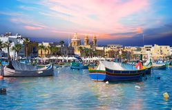 Marsaxlokk village harbor of Malta with boats on sea. Marsaxlokk village harbor of Malta, illuminate by sunset light. Travel destination to the most beautiful Royalty Free Stock Image