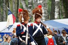 Marsch mit zwei Soldaten mit Gewehr und Flagge. Lizenzfreie Stockbilder
