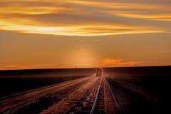 MARSCHERA 8, 2017, NEBRASKA - solnedgång över den lantliga lantgårdlandsvägen med pickupet som kör förbi rad av powerlines Arkivbild