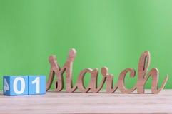 Marschera 1st dag 1 av månaden, daglig träkalender på tabellen och göra grön bakgrund Vårtid, tömmer utrymme för text Arkivfoton