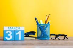 Marschera 31st dag 31 av månaden, kalender på ljus - gul bakgrund, arbetsplats med kontorssuplies Vårtid som är tom Arkivfoton