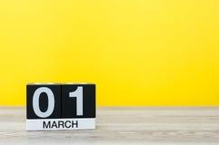 Marschera 1st dag 1 av månaden, kalender på tabellen med gul bakgrund Vårtid, tömmer utrymme för text Royaltyfri Fotografi
