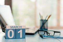 Marschera 1st dag 1 av månaden, kalendern på bakgrund för affärskontor, arbetsplatsen med bärbara datorn och exponeringsglas Vårt Royaltyfria Foton