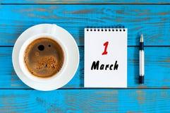 Marschera 1st dag 1 av månaden, kalendern som är skriftlig, och morgonkaffekoppen på blå träbakgrund Vårtid, bästa sikt Fotografering för Bildbyråer