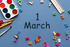 Marschera 1st dag 1 av marschmånaden, kalender på blå bakgrund med skolatillförsel Vårtid, bästa sikt Royaltyfri Foto