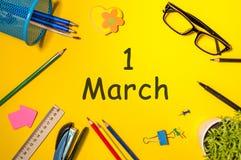 Marschera 1st dag 1 av marschmånaden, kalender på gul bakgrund med kontorstillförsel Vårtid, bästa sikt Royaltyfri Bild