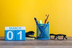 Marschera 1st dag 1 av marschmånaden, kalendern på tabellen med gul bakgrund och kontoret eller skolatillförsel Fjädra den tid… r Royaltyfria Foton