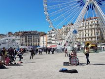 Marseille. France - 05.08.2017: Bright sunny day. Street musicians on the embankment of the Old Port entertain tourists. Near the Ferris wheel stock images