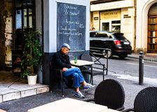 Marseille, France - 2019.Old man drinking a beer on a terrace in downtown Marseilles.  royalty free stock photography