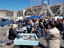 Marseille Frankrike - 05 08 2017: Ljus solig dag Lås för morgon för fiskareförsäljning nytt av fisken på invallningen royaltyfri foto