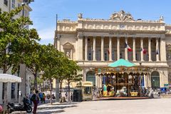 Marseille Stock Exchange building architecture. Carousel is waiting for children after school in front of Stock Exchange building at Marseille, south of France stock photo