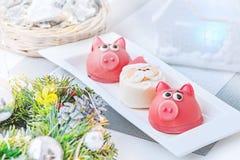 Marsepein in de vorm van het symbool van het nieuwe jaarroze - varken, zoete gevoelige makarons, heemst, pinda's in suikerpastelk stock afbeelding