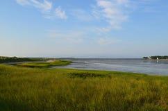 Marsh Grass on Duxbury Bay. Summer skies over Duxbury Bay with marsh grass and sand Stock Photos
