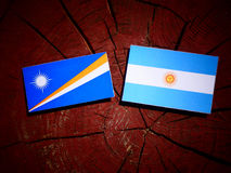 Marshall Islands flag with Argentinian flag on a tree stump isol Stock Image