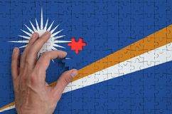 Marshall Islands flag is depicted on a puzzle, which the man`s hand completes to fold.  stock illustration
