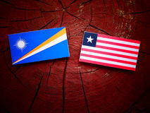 Marshall Islands flag with Liberian flag on a tree stump isolate. D Royalty Free Stock Photo