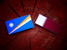 Marshall Islands flag with Qatari flag on a tree stump isolated. Marshall Islands flag with Qatari flag on a tree stump Royalty Free Stock Image