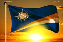 Marshall Islands flag weaving on the beautiful orange sunset with clouds background. Marshall Islands flag weaving on the beautiful orange sunset background stock photos