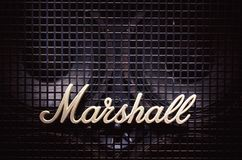 Marshall Logo on Bass Speaker. Cacak, Serbia - December 13, 2017: Marshall logo on old bass speaker with metal net in front of woofers Royalty Free Stock Photos