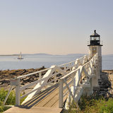 Marshall Point Lighthouse Port Clyde Maine, USA. Wide-angle square view of Marshall Point Lighthouse looking toward Penobscot Bay with sailboat, Port Clyde, St Royalty Free Stock Photos