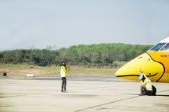 Marshalling tailandês do marshaller dos aviões e sinal visual entre os pessoais e os pilotos à terra no avião na pista de decolag Fotos de Stock