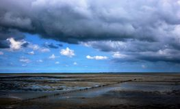 Marshes in Holland. The tide is ebb. In the foreground there are muddy marshes with breakwaters. In the background there is a moody blue sky with grey clouds royalty free stock photos