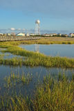 Marshes near the Intracoastal waterway. Marshes and seagrass adjacent to the Intracoastal waterway with Surfcity water tower in the background and long boardwalk Stock Photo